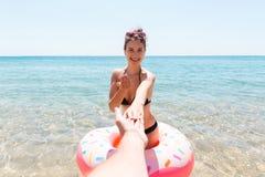 Suivez-moi concept de vacances La femme appelle pour nager en mer et ondule sa main Fille d?tendant sur l'anneau gonflable en mer images stock