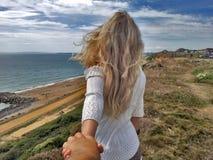 Suivez-moi Fille blonde reculant sur la falaise de bord Images libres de droits