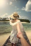Suivez-moi Fille dans la robe blanche sur le pont maldives tropiques Océan Image stock