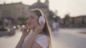 Suivez-moi ! fille drôle marchant dans la ville, début de la matinée la femme dans de grands écouteurs réclame elle-même 4K banque de vidéos