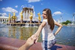 Suivez-moi La jeune fille heureuse tire la main de types Photo stock