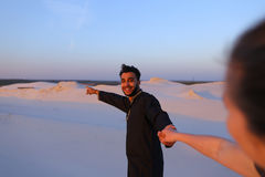Suivez-moi type arabe et femme européenne qui marche à la main dans le deser Photo stock