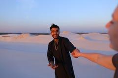 Suivez-moi type arabe et femme européenne qui marche à la main dans le deser Photographie stock libre de droits