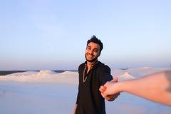 Suivez-moi type arabe et femme européenne qui marche à la main dans le deser Photographie stock