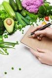 Suivez un régime la nourriture Planification du produit d'écriture de femme sur le papier Photo libre de droits
