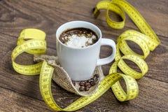 Suivez un régime le café avec de la crème dans une tasse blanche avec le ruban métrique photo stock