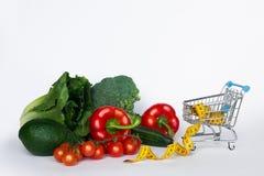 Suivez un régime le concept Légumes frais dans un caddie et une bande de mesure jaune Nourriture saine et nutrition appropriée Ma images libres de droits