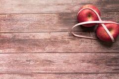 Suivez un régime le grippage rouge de pomme avec la bande de mesure sur le concept en bois de la vie de santé et de forme physiqu Photographie stock