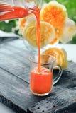 Suivez un régime le jus de carotte frais versé du broc dans la tasse en verre sur un fond des roses jaunes Copiez l'espace Photo libre de droits