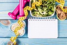 Suivez un régime le plan, le menu ou le programme, le ruban métrique, les haltères et la nourriture de régime, la perte de poids  photographie stock