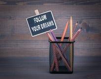 Suivez vos rêves Une petite craie de tableau noir et un crayon coloré sur le fond en bois Photo libre de droits