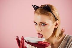Suivre un régime et santé Fille dans des oreilles de chaton et des gants rouges avec du yaourt sur le fond rose La femme sexy de  photos libres de droits