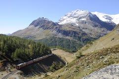 Suiza: El Bernina-tren está curvando a través de las montañas suizas Foto de archivo libre de regalías