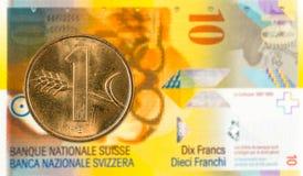 1 suizo rappen la moneda contra billete de banco del franco suizo 10 foto de archivo
