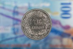 2 suizos Franc Coin con 100 suizos Franc Bill como fondo Foto de archivo libre de regalías