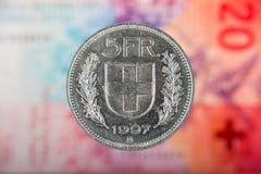 5 suizos Franc Coin con 20 suizos Franc Bill como fondo Fotos de archivo