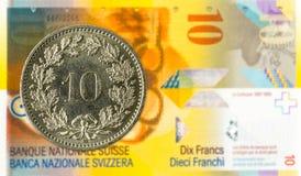 10 suizos rappen la moneda contra billete de banco del franco suizo 10 foto de archivo