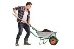 Sujeira da carga do trabalhador em um carrinho de mão Imagem de Stock