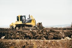 Sujeira movente e terra da mini escavadora industrial com colher Detalhes industriais de ajardinar Imagens de Stock