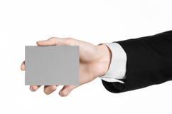 Sujet d'affaires et de publicité : Homme dans le costume noir jugeant un disponible gris de carte vierge d'isolement sur le fond  Photos libres de droits