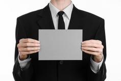 Sujet d'affaires et de publicité : Homme dans le costume noir jugeant un disponible gris de carte vierge d'isolement sur le fond  Photos stock
