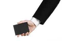 Sujet d'affaires et de publicité : Homme dans le costume noir jugeant un disponible noir de carte vierge d'isolement sur le fond  photographie stock libre de droits