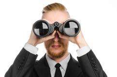 Sujet d'affaires et de recherche : L'homme dans le costume noir jugeant les jumelles noires disponibles sur le blanc a isolé le f images stock