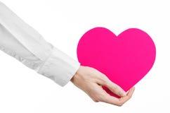 Sujet de maladie cardiaque et de santé : remettez le docteur dans une chemise blanche jugeant une carte sous forme de coeur rose  Image stock