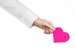 Sujet de maladie cardiaque et de santé : remettez le docteur dans une chemise blanche jugeant une carte sous forme de coeur rose  Photo stock