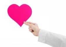 Sujet de maladie cardiaque et de santé : remettez le docteur dans une chemise blanche jugeant une carte sous forme de coeur rose  Images stock