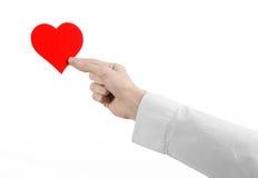 Sujet de maladie cardiaque et de santé : remettez le docteur dans une chemise blanche jugeant une carte sous forme de coeur rouge Photos libres de droits