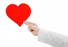 Sujet de maladie cardiaque et de santé : remettez le docteur dans une chemise blanche jugeant une carte sous forme de coeur rouge Image stock