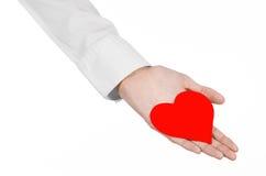 Sujet de maladie cardiaque et de santé : remettez le docteur dans une chemise blanche jugeant une carte sous forme de coeur rouge Photographie stock