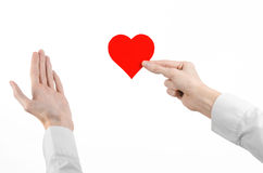 Sujet de maladie cardiaque et de santé : remettez le docteur dans une chemise blanche jugeant une carte sous forme de coeur rouge Photo stock