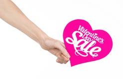 Sujet de Saint-Valentin et de vente : Remettez tenir une carte sous forme de coeur rose avec la vente de mot d'isolement sur le f Photo stock