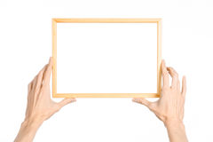 Sujet de vue de décoration et de photo de Chambre : main humaine jugeant un cadre de tableau en bois d'isolement sur un fond blan photographie stock libre de droits