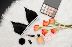 Sujetador negro del cordón en la piel blanca Rosas, lápiz labial, perfume y sombra de ojos anaranjados concepto de moda Foto de archivo libre de regalías