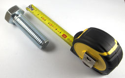 Sujete con cinta adhesiva la regla y el tornillo Imagenes de archivo