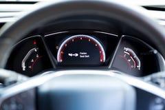 Sujete la señal de peligro del cinturón de seguridad en la información del tablero de instrumentos del coche para s Foto de archivo libre de regalías