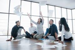 Sukces strategia wpólnie Rozochoceni biznesowi koledzy podrzuca papiery przy kreatywnie biurem Współpraca korporacyjny zdjęcie royalty free