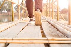 sukcesu mężczyzna odprowadzenie, podróżnika mężczyzna chodzi sukces na długim drewnianym bambusa moscie Zdjęcia Stock