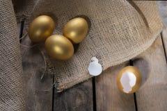Sukcesu symbol lub Szczęśliwy Wielkanocny pojęcie Opróżnia Łamanego Dużego Złotego jajko na nieociosanym drewnianym naturalnym tl zdjęcie royalty free