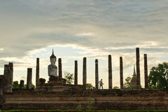 Sukhothai Historical Park, Thailand. A man standing in front of Buddha image Stock Image