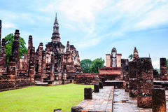 Sukhothai style chedi and standing buddha image Stock Photo