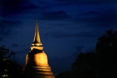 Sukhothai Thailand at night. Location is Sukhothai, Thailand, Asia, World Heritage Site, the old capitol city of Thailand. A temple steeple lit with dark bluish Royalty Free Stock Photography