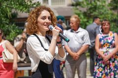 Young female singer with beautiful red hair singing in the street on the background of people. royalty free stock photo