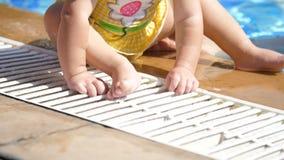 Sul bordo, vicino allo stagno si siede un bambino di un anno, bambino, scalzo, in un costume da bagno stock footage