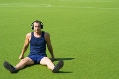 Sul campo di football americano, una seduta dell'uomo Immagine Stock