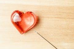 Sul cuore di legno e sull'ago dei gioielli del fondo, medici fotografie stock