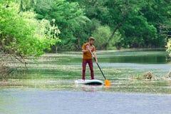 Sul fiume nella distanza un uomo nuota su un bordo del sup fotografia stock libera da diritti